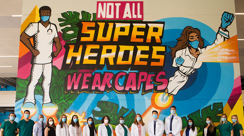 preceptors in front of super heroes mural