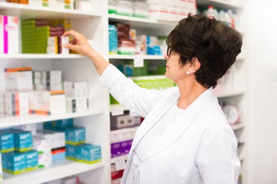 pharmacist picking meds on shelf