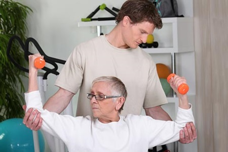 rehab therapist and patient with free weights